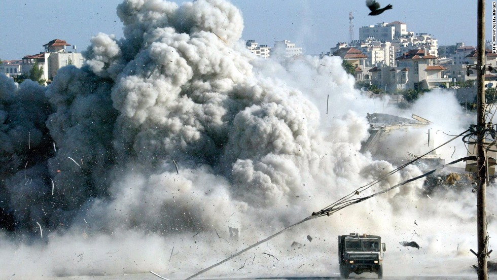 A large explosion rocks Arafat's headquarters in Ramallah moments after Israeli troops blew up a building on September 20, 2002. It was the start of a 10-day siege.