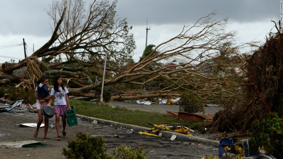 Women walk past fallen trees and destroyed houses in Tacloban on November 9. Residents scoured supermarkets for water and food as they slowly emerged on streets littered with debris.