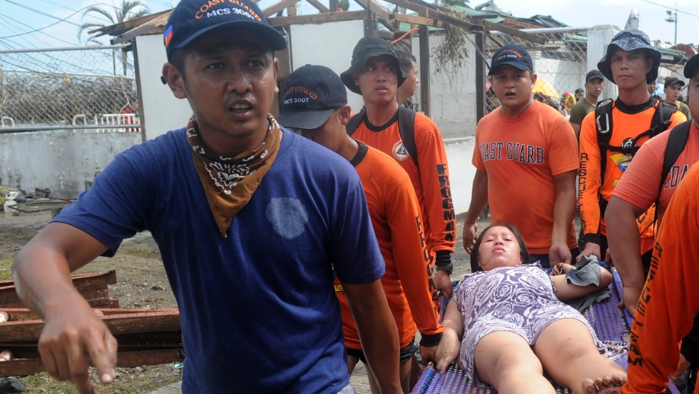 Rescue workers carry a woman about to give birth November 9 at a makeshift medical center at the Tacloban airport.