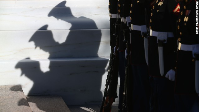 Members of the military stand at attention before a ceremony at the Tomb of the Unknowns.