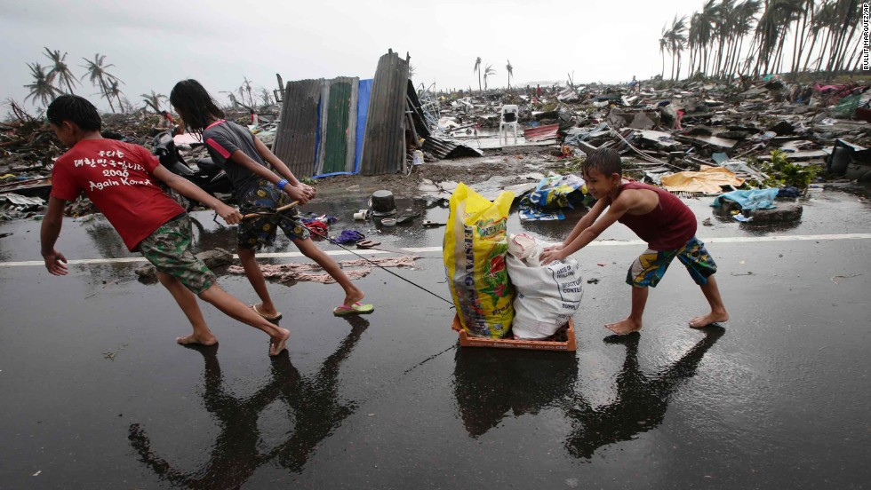 Children carry relief goods past damaged homes in Tacloban on November 10.