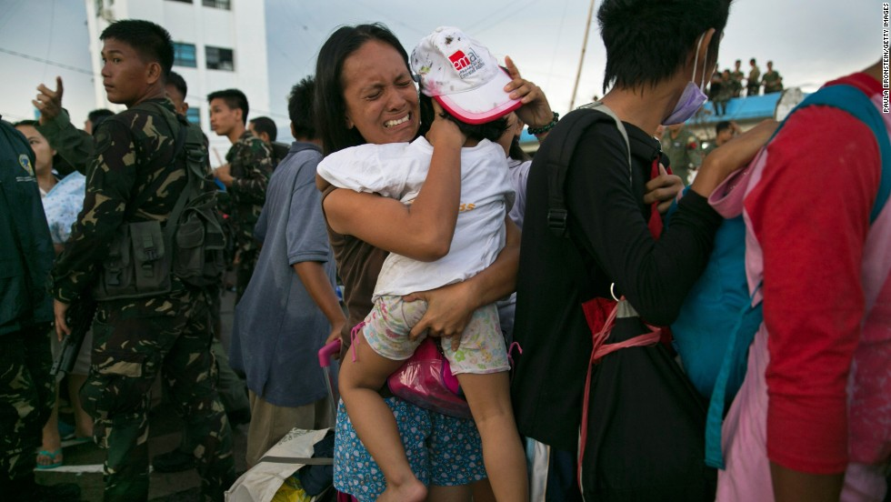 A woman carrying a child cries November 12 as survivors wait to board an aircraft in Tacloban.