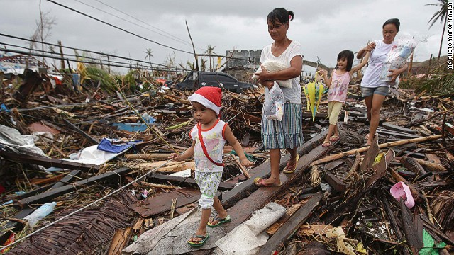 Survivors walk in typhoon ravaged Tacloban city, Leyte province, central Philippines on Tuesday, Nov. 12, 2013.