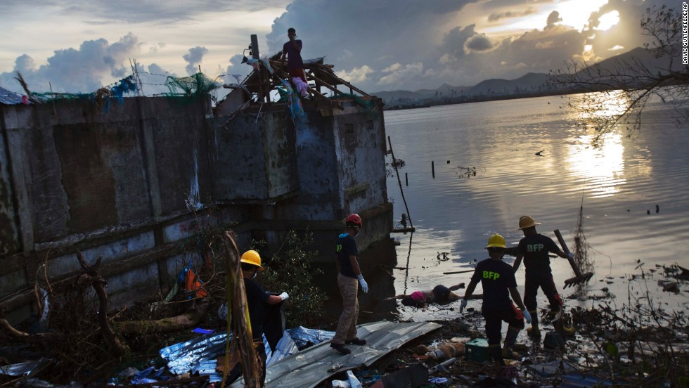 A rescue team wades into Tacloban floodwater to retrieve a body on November 13.