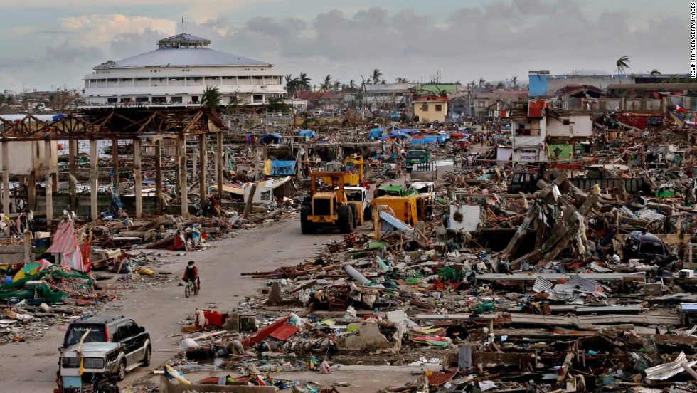 Residents make their way through a destroyed neighborhood in Tacloban on November 13.