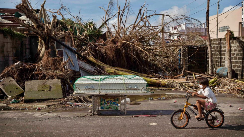 A boy rides his bike past a coffin and other scenes of destruction Wednesday, November 13, in Tacloban.