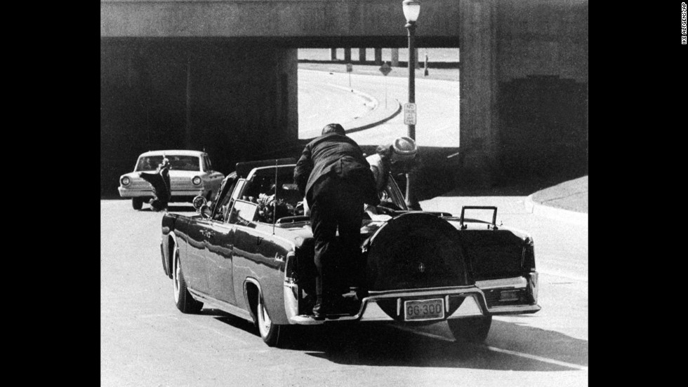 Kennedy slumps in the back seat of the car and his wife leans over to him as Secret Service Agent Clinton Hill rides on the back of the car.