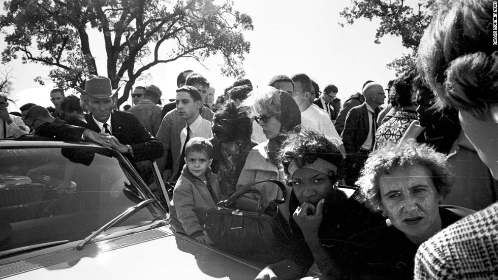 Hurchel Jacks, Vice President Johnson's driver in the motorcade, listens with others to news accounts on the car radio outside the Parkland Hospital emergency entrance. After the shots were fired, Jacks had rerouted the vice president's car to safety. The ABC radio network broadcast the first nationwide news bulletin reporting that shots have been fired at the Kennedy motorcade.