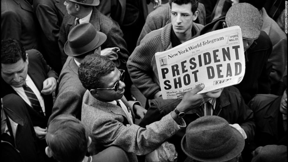 A man holds up a copy of the New York World-Telegram featuring the news of the assassination. Major television and radio networks devote continuous news coverage to the events of the day, canceling all entertainment and all commercials. Many theaters, stores and businesses, including stock exchanges and government offices, are closed.