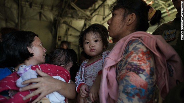 Typhoon victims board a Philippines C130 army cargo plane as she and others are evacuated, at Tacloban airport on November 14, 2013.