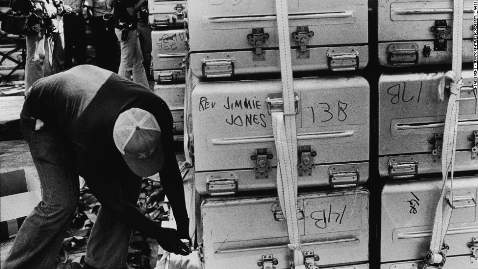 An unidentified man straps a stack of aluminum coffins for shipment to the United States.