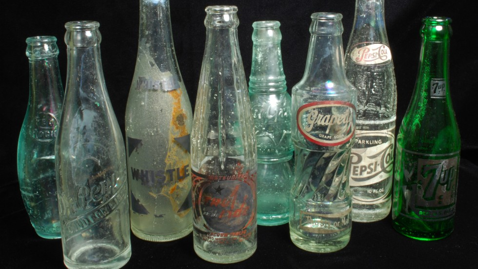 1885-1966: A sample of the recovered soft-drink bottles. The bottling industry first used applied color labels in 1934.