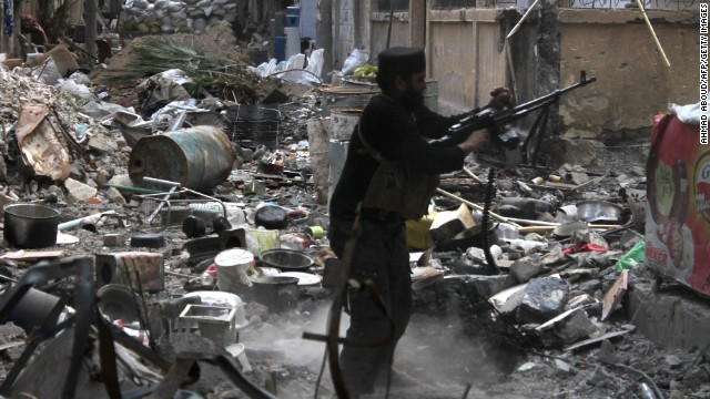 A rebel fighter fires his weapon as he stands amidst rubble and debris during clashes with Syrian government forces in Deir Ezzor, Syria on November 11.