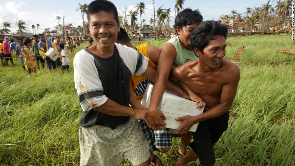 Typhoon victims in Salcedo, Philippines, hold onto a box of relief goods received November 16 from a U.S. Navy helicopter.