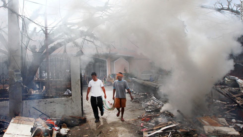 Men walk through smoke as they burn debris from a Tacloban church on November 16.