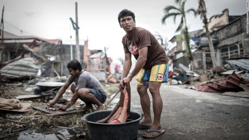 A man in Tanauan cleans meat after slaughtering his only cow that survived the typhoon.
