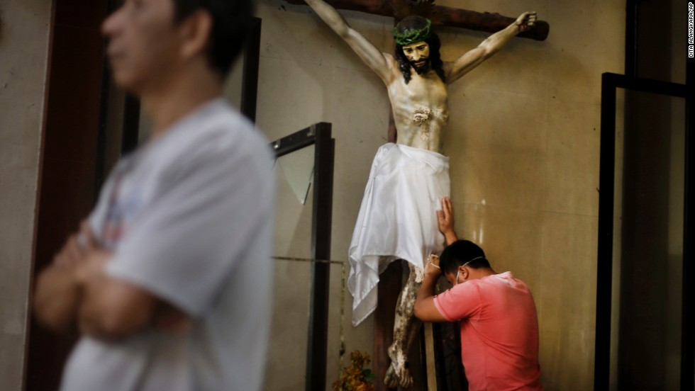 A man leans against a statue of the Crucifixion before a Mass at Santo Nino Church in Tacloban on November 17.