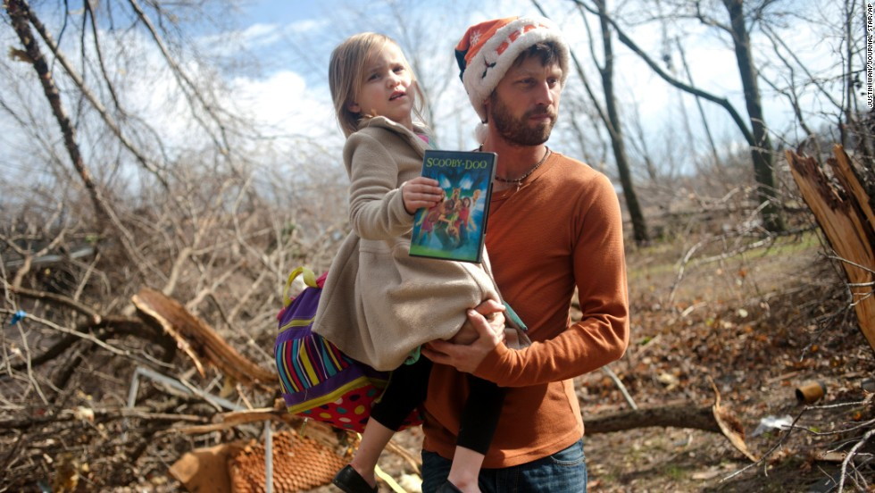 Billy Vestal evacuates his home in East Peoria, Illinois, with his 3-year-old daughter, Lillian Vestal, after a tornado damaged the area on November 17.