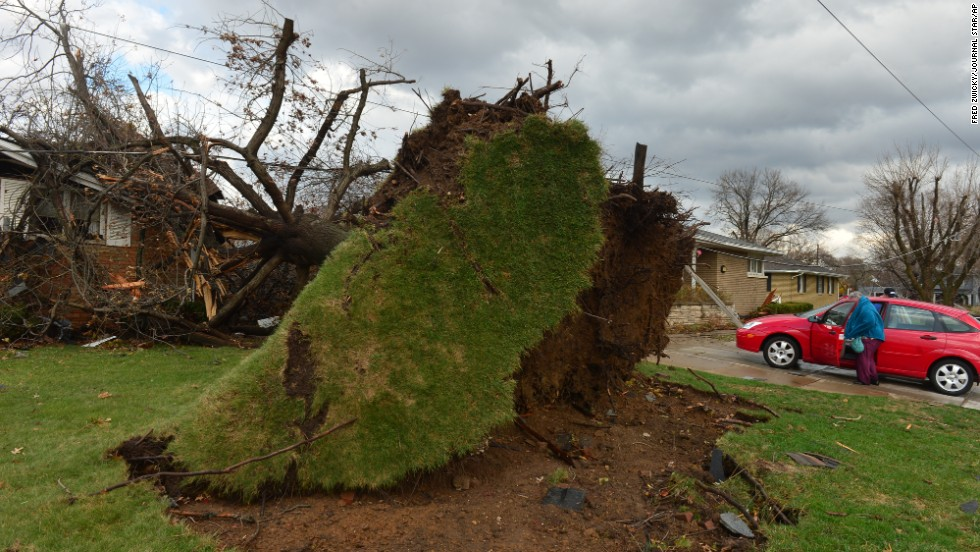 A home is damaged by a tree that was uprooted during the storm in Pekin on November 17. Pekin is part of the cluster of towns in central Illinois hit hard by the severe weather.