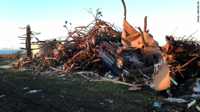 An overturned car rests in a pile of rubble about a mile northeast of Washington, Illinois, on November 17.