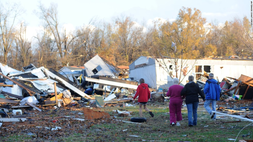 An elderly woman is escorted through tornado debris in Brookport, Illinois, on November 17.