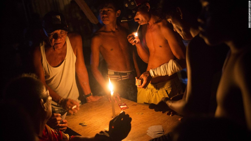 People play cards by candlelight Monday, November 18, in Tacloban.