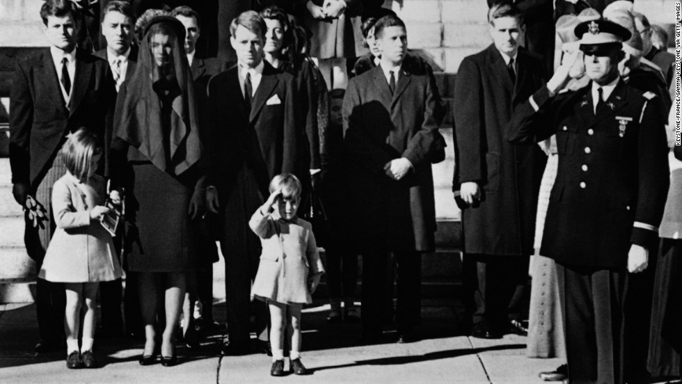 During her father's funeral in 1963, Caroline stands next to her mother as her brother salutes her father's coffin.