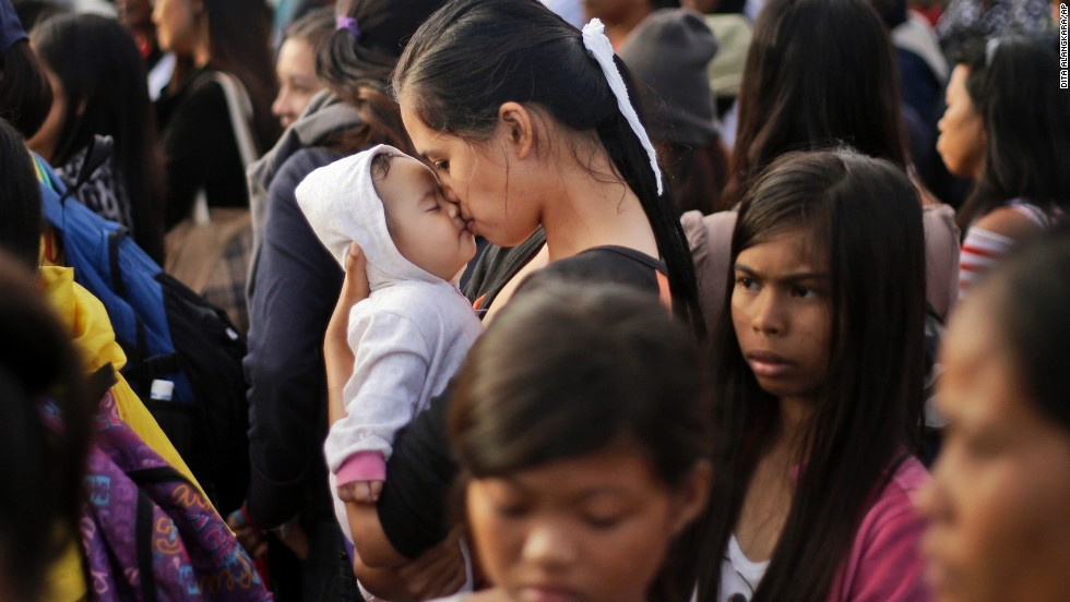 A typhoon survivor kisses her baby as she waits to board her evacuation flight at the airport in Tacloban on Friday, November 22.