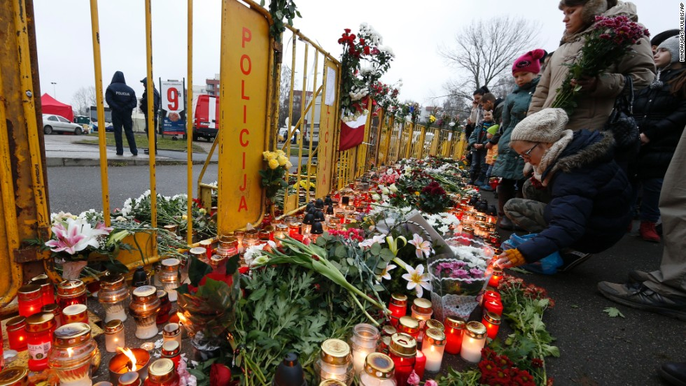 People place flowers and light candles in front of the Maxima supermarket in Riga, Latvia, on Saturday, November 23, two days after dozens of people reportedly died in a roof collapse. Riga Mayor Nils Usakovs said authorities suspect building materials stored on the roof caused it to collapse Thursday.