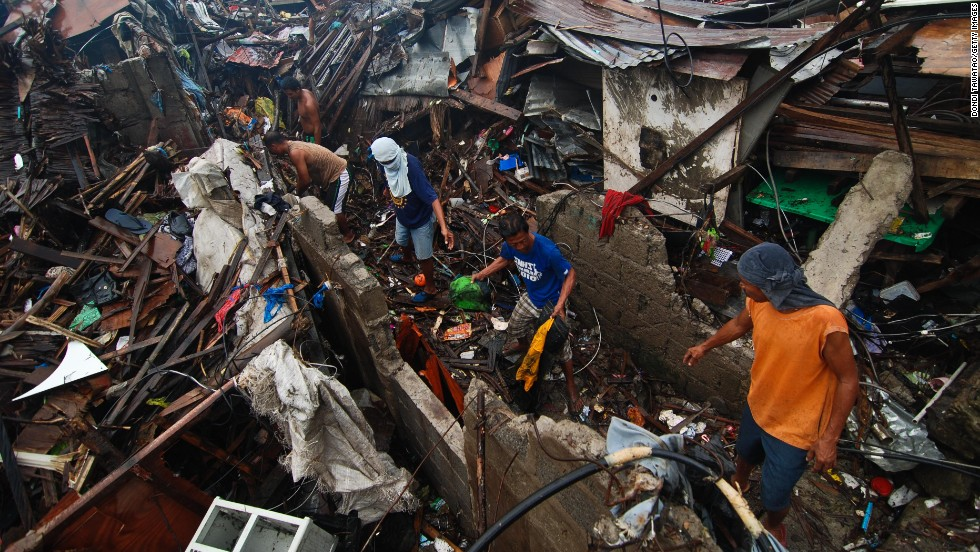 Groups of men clear debris near the shoreline on November 23 in Tacloban.