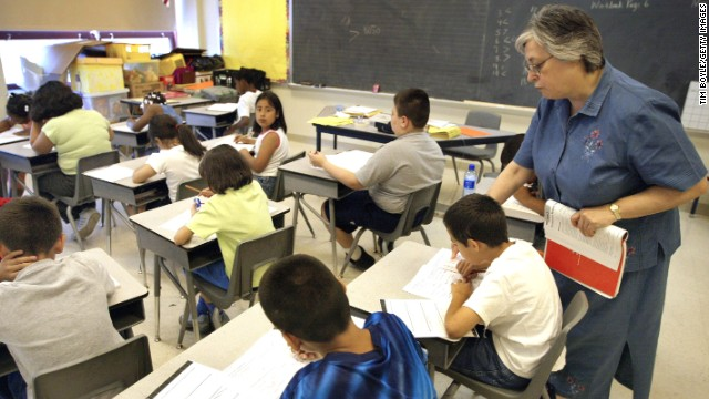A teacher assists third-grade students in a Chicago classroom. Illinois is one of 45 states that have adopted Common Core.