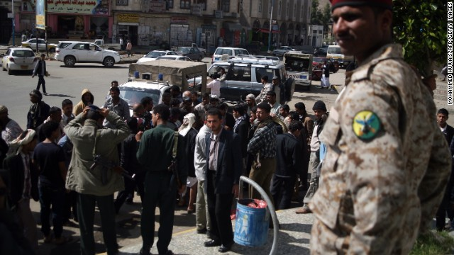 A soldier stands guard as onlookers gather following a shooting incident targeting two Russians on November 26, 2013 in Sanaa.