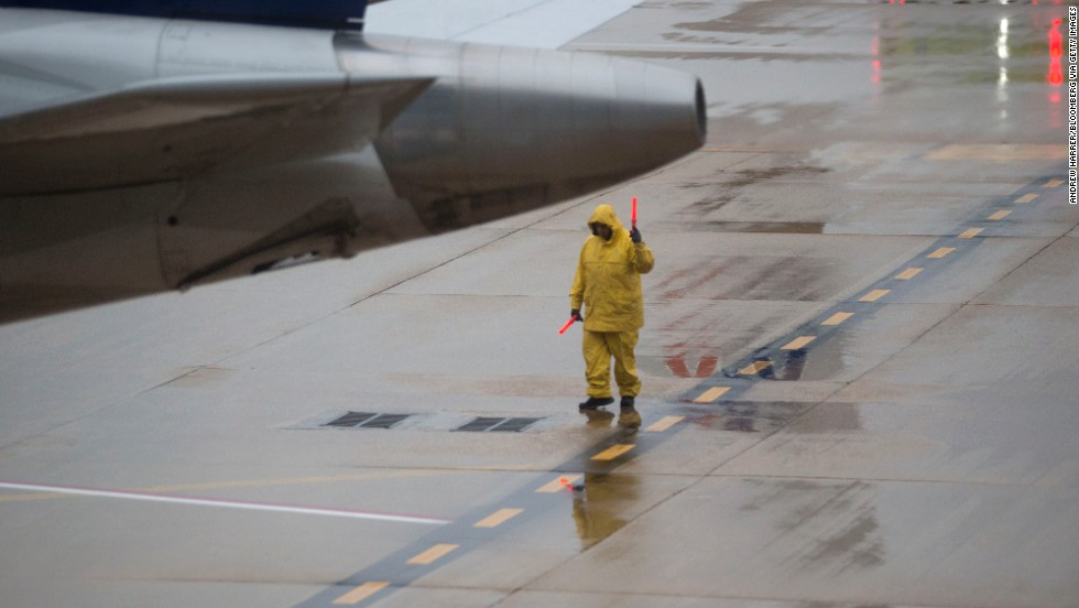 An employee signals a plane out of the gate at Ronald Reagan National Airport outside of Washington on Tuesday, November 26.