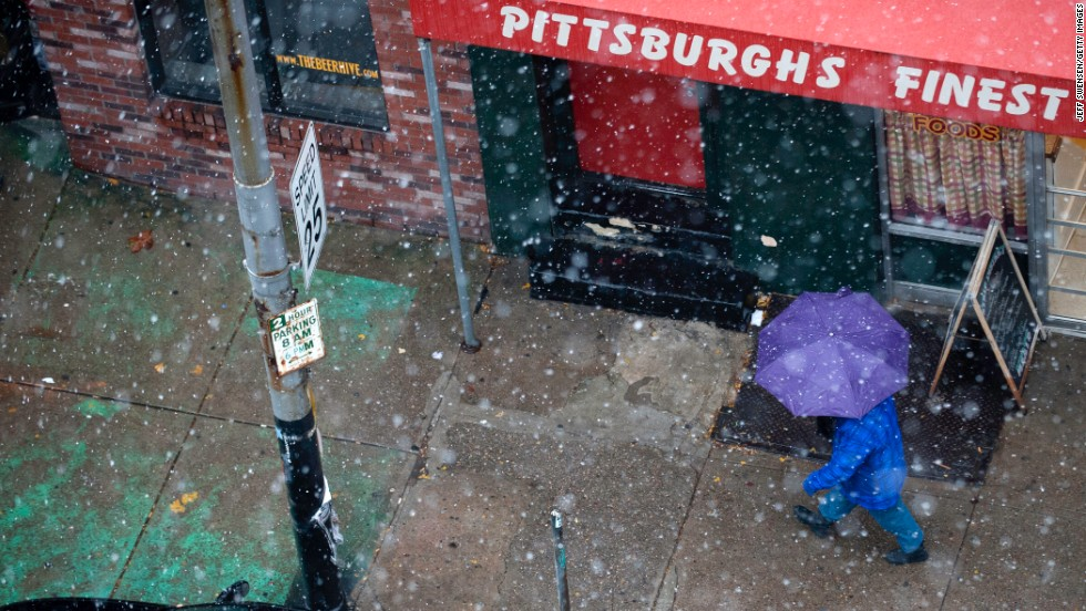 A pedestrian walks through snow showers along Penn Ave in Pittsburgh on November 26.