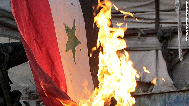 A rebel fighter burns a Syrian flag found in a building that belonged to Syrian government forces in the northern city of Aleppo on November 21, 2013. Fighting for a key military base outside Syria's main northern city of Aleppo killed at least 15 pro-government militiamen, the Syrian Observatory for Human Rights said.