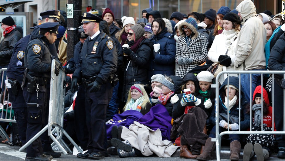 Police officers adjust a barricade as people wait in cold weather along the route of the Macy's Thanksgiving Day Parade on Thursday, November 28, in New York.