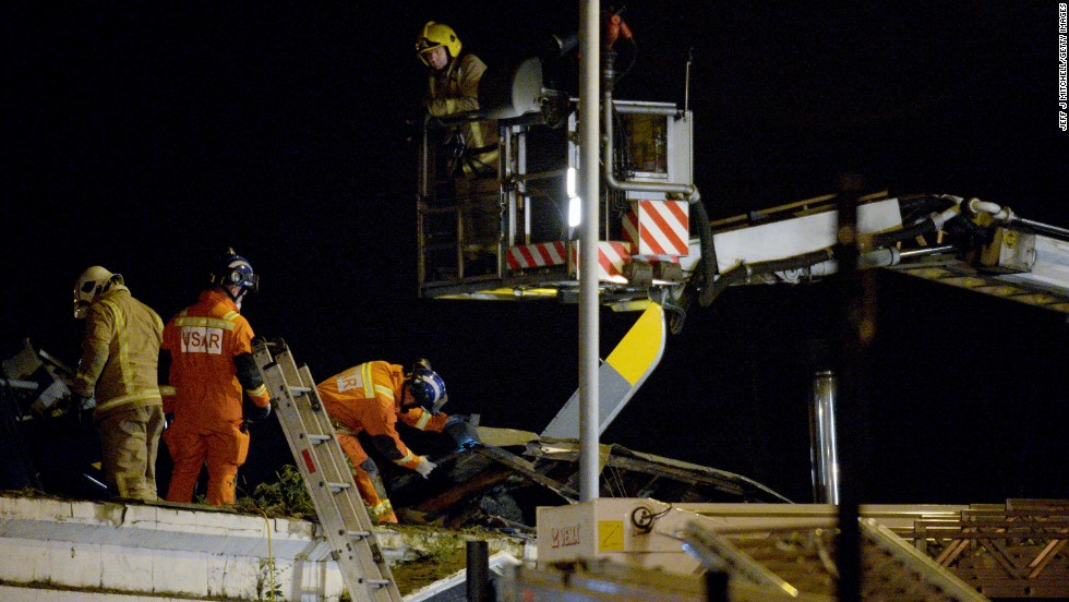 Emergency responders work on the wreckage on top of the pub.