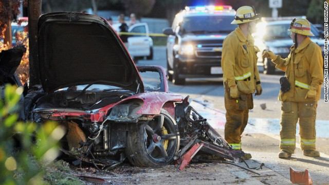 First responders gather evidence near the wreckage of a Porsche sports car that crashed into a light pole on Hercules Street near Kelly Johnson Parkway in Valencia, California, on Saturday, November 30. Actor Paul Walker reportedly was a passenger in the car.