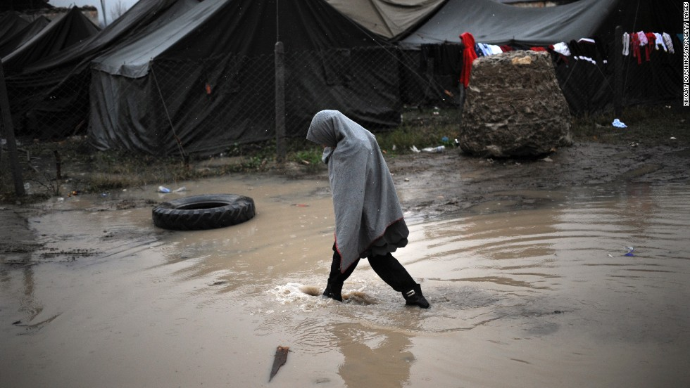A girl crosses a puddle during the first snowfall of the season in a refugee camp in Harmanli, Bulgaria, on Wednesday, November 27.