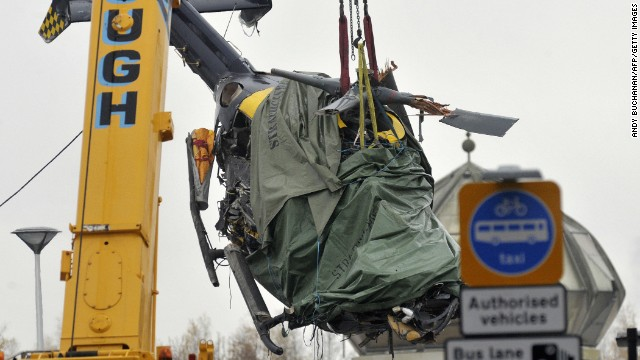 The wreckage of a police helicopter is winched from the collapsed roof of a pub in Glasgow on December 2, 2013.