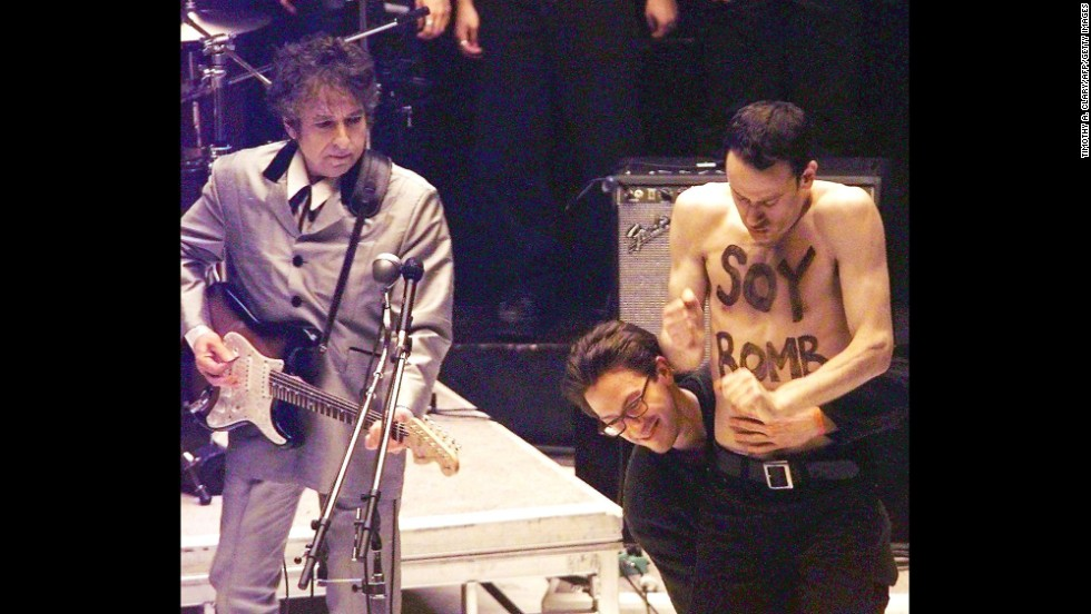 Performance artist Michael Portnoy is taken off stage during Dylan's performance at the Grammy Awards in 1998. Portnoy had been hired as part of the background dancers for the performance, but his shirtless interruption was not planned and he was carted off stage.