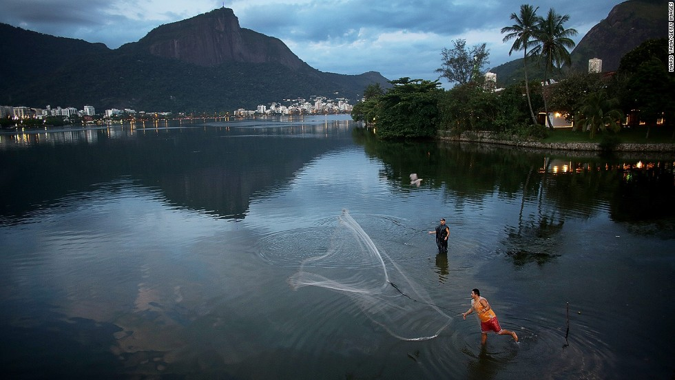 "DECEMBER 4 - LAGOA RODRIGO DE FREITAS, BRAZIL: A fisherman tosses his net into Brazil's Lagoa Rodrigo de Freitas, which will host the rowing and canoeing events at the Rio 2016 Olympic Games. In the waters around the future Olympic Park, <a href=""http://sportsillustrated.cnn.com/2013/olympics/wires/11/20/2080.ap.oly.rio.2016.dirty.olympics/index.html#ixzz2mVk1jM5a"">the average fecal pollution rate is 78 times that of the Brazilian government's ''satisfactory'' limit, </a>but Rio's Olympic committee has pledged in writing that the pollution problems will be fixed as part of the Games' legacy."