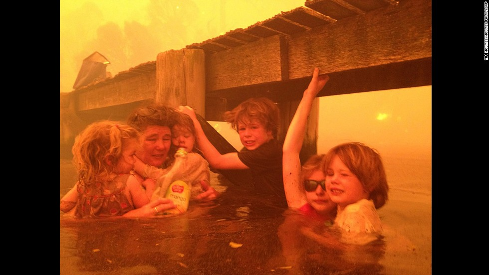 <strong>January 4:</strong> Tammy Holmes and her grandchildren take refuge under a jetty as a wildfire rages nearby in the Tasmanian town of Dunalley, Australia.