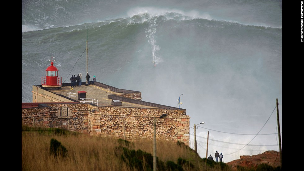 <strong>January 28:</strong> A crowd in Nazare, Portugal, watches as surfing legend Garrett McNamara appears to break his own world record for the biggest wave ever surfed. The wave was estimated to be about 100 feet high.