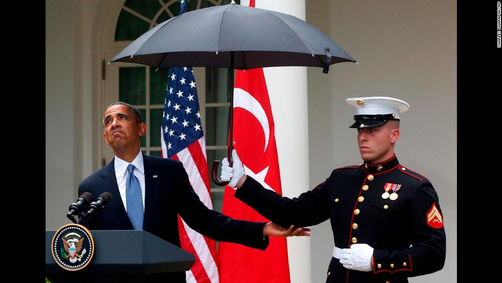 <strong>May 16:</strong> U.S. President Barack Obama looks to see if it is still raining as a Marine holds an umbrella for him during a news conference in the Rose Garden of the White House.