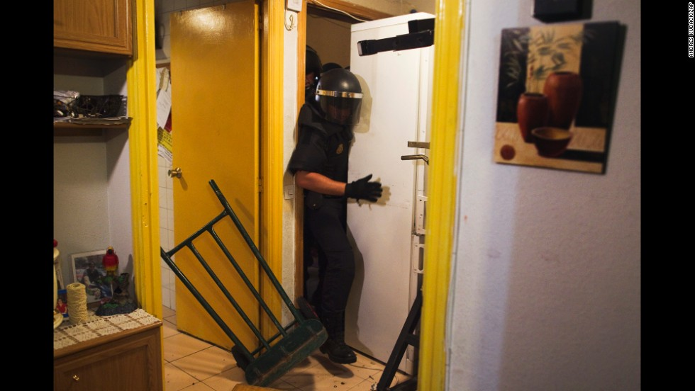 <strong>September 25:</strong> Police push away a refrigerator as they enter the Madrid apartment of Maria Isabel Rodriguez Romero. Romero and her family of six were evicted by the State City Hall Housing Company. Spain is slowly emerging from a two-year recession, but it still has a high unemployment rate and evictions have rapidly increased as borrowers are unable to pay their mortgages.