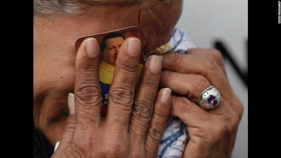 <strong>March 6:</strong> A crying woman holds a picture of Venezuelan President Hugo Chavez outside the military hospital where he died one day earlier in Caracas, Venezuela. Chavez, who had battled cancer, was 58.