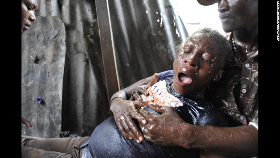 <strong>September 30:</strong> A woman in Port-au-Prince, Haiti, suffers an asthma attack after tear gas was used during an anti-government demonstration on the anniversary of the 1991 coup against former President Jean-Bertrand Aristide.