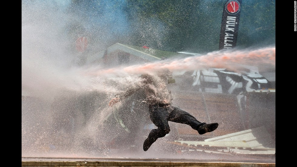 <strong>June 11:</strong> A protester is hit by a water cannon during clashes in Taksim Square in Istanbul.