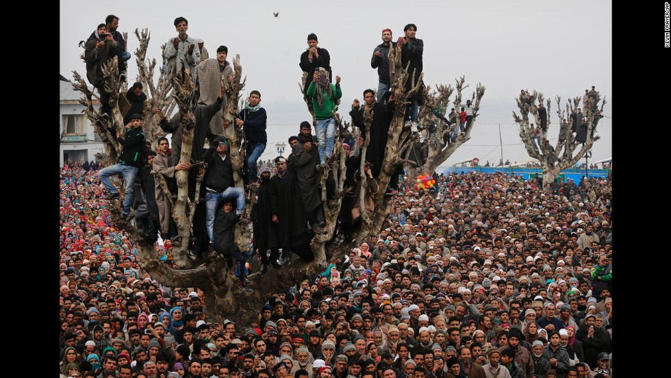<strong>February 1:</strong> Kashmiri Muslims stand on a tree as they offer prayers at the Hazratbal Shrine in Srinagar, India.